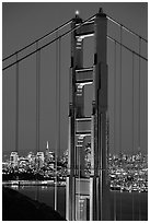 The city seen through the cables and pilars of the Golden Gate bridge, night. San Francisco, California, USA ( black and white)
