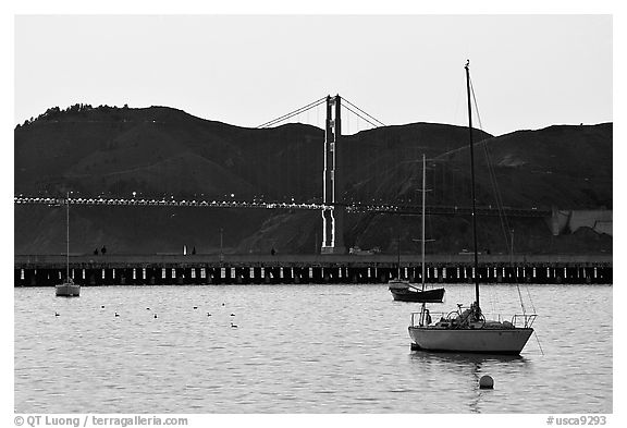 Sailboat in the Marina, with Golden Gate Bridge at sunset in the background. San Francisco, California, USA (black and white)
