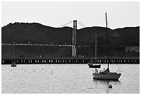 Sailboat in the Marina, with Golden Gate Bridge at sunset in the background. San Francisco, California, USA ( black and white)