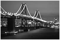 Bay Bridge seen from Treasure Island with defocused lights, sunset. San Francisco, California, USA ( black and white)