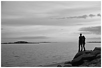 Couple standing on rock and Atlantic Ocean at sunset, Westbrook. Connecticut, USA ( black and white)