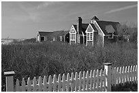 Fence and cottages in winter, Truro. Cape Cod, Massachussets, USA ( black and white)