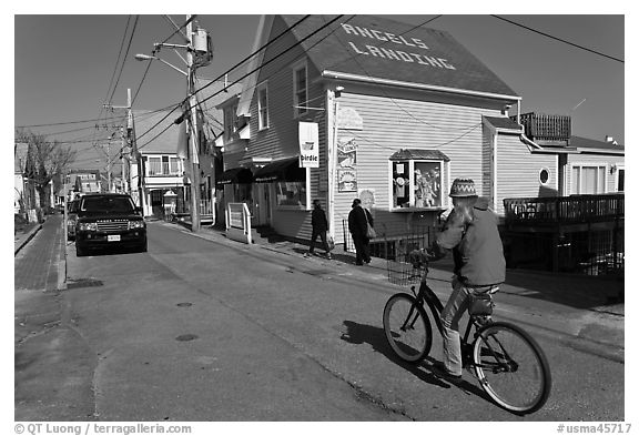 Woman biking on main street, Provincetown. Cape Cod, Massachussets, USA (black and white)