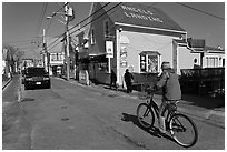 Woman biking on main street, Provincetown. Cape Cod, Massachussets, USA ( black and white)
