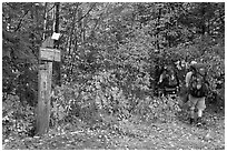 Backpackers hiking into autumn woods at Appalachian trail marker. Maine, USA ( black and white)