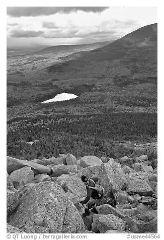 Hiker descends from summit amongst boulders above treeline. Baxter State Park, Maine, USA (black and white)