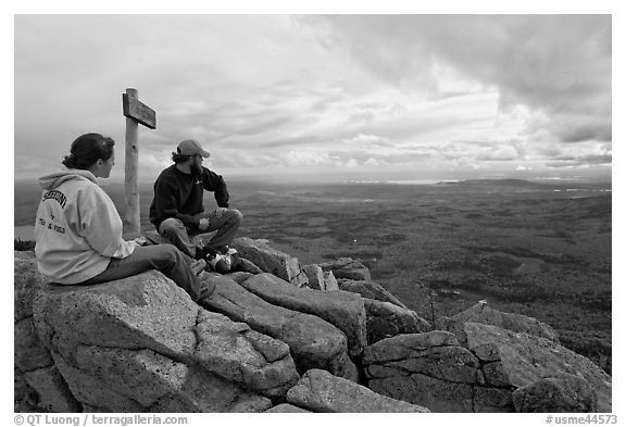 Hikers taking in view near sign marking summit of South Turner Mountain. Baxter State Park, Maine, USA (black and white)