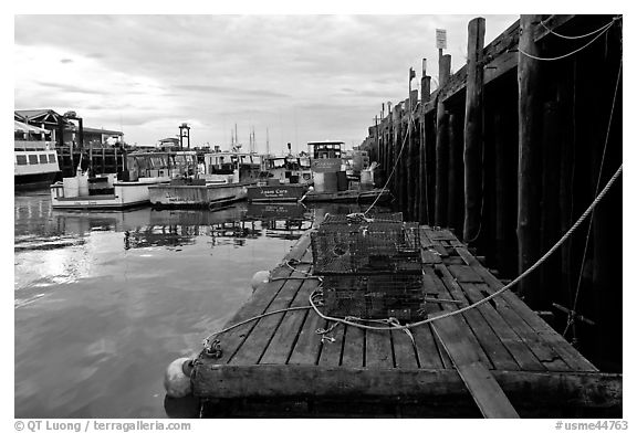 Lobster traps and fishing boats below pier. Portland, Maine, USA (black and white)