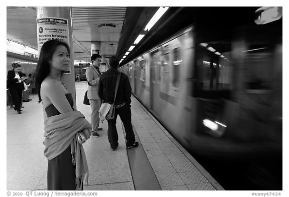 Young woman and arriving train on subway platform. NYC, New York, USA (black and white)