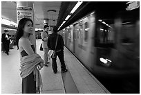 Young woman and arriving train on subway platform. NYC, New York, USA ( black and white)
