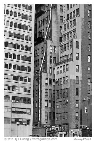 Old high-rise buildings with exterior pipe. NYC, New York, USA (black and white)