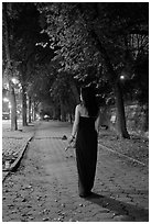 Woman in evening dress with rose on alley bordering Central Park at night. NYC, New York, USA ( black and white)