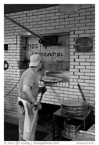Man loading pizza into oven, Lombardi pizzeria. NYC, New York, USA (black and white)