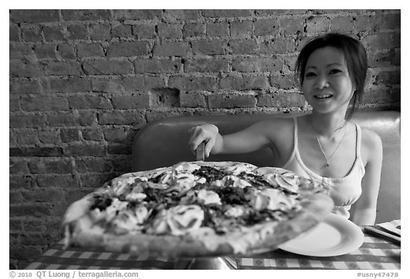 Woman getting slice of pizza at Lombardi. NYC, New York, USA (black and white)