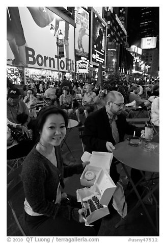 Woman with cupcakes sitting on Times Squares at night. NYC, New York, USA (black and white)