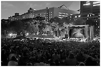 Outdoor musical performance at night with QTL photo as screen backdrop, Central Park. NYC, New York, USA (black and white)