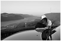 Couple embracing on car hood, with view of mouth of river gorge. Columbia River Gorge, Oregon, USA (black and white)