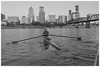 Woman rowing on racing shell and city skyline at sunrise. Portland, Oregon, USA (black and white)
