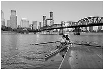 Rowers on double-oar shell lauching from deck in front of skyline. Portland, Oregon, USA (black and white)