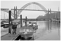 Couple holds  small boat on pier, Newport Marina. Newport, Oregon, USA (black and white)