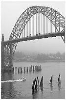 Small boat heading towards ocean under Yaquina Bay Bridge. Newport, Oregon, USA (black and white)