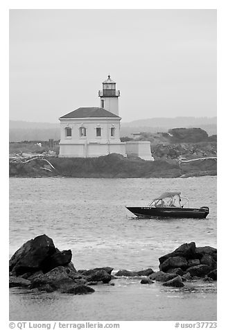 Small boat and Coquille River lighthouse. Bandon, Oregon, USA (black and white)