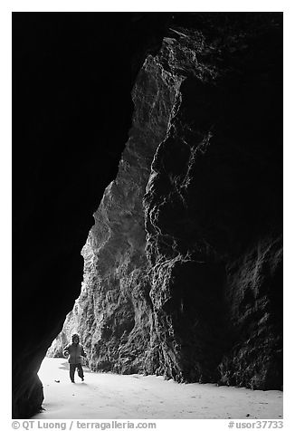 Infant walking into sea cave. Bandon, Oregon, USA (black and white)