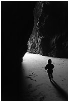 Infant walking towards the light in sea cave. Bandon, Oregon, USA (black and white)