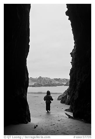 Infant standing at sea cave opening. Bandon, Oregon, USA