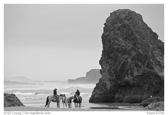 Women ridding horses next to sea stack. Bandon, Oregon, USA
