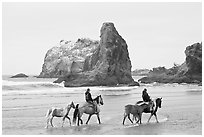 Women horse-riding on beach. Bandon, Oregon, USA (black and white)