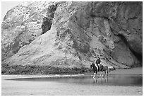 Woman horse-riding on beach next to sea cave entrance. Bandon, Oregon, USA ( black and white)