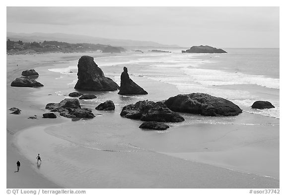 Beach at Face Rock with two people walking. Bandon, Oregon, USA (black and white)