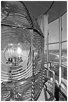 Rotating light inside Cape Blanco Lighthouse tower and landscape. Oregon, USA (black and white)