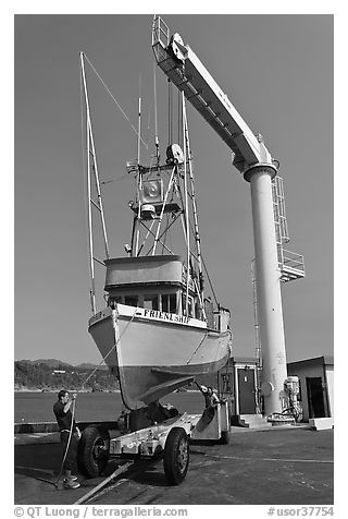 Fishing boat lifted from water by huge hoist, Port Orford. Oregon, USA (black and white)