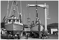 Fishing boats parked on deck with hoist behind, Port Orford. Oregon, USA (black and white)