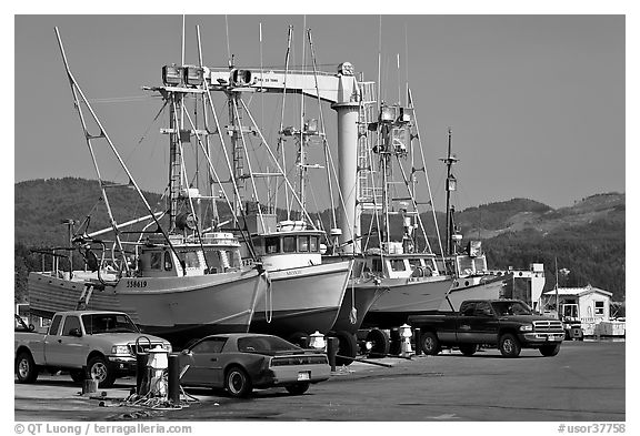Fishing boats and cars parked on deck, Port Orford. Oregon, USA (black and white)