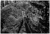 Hiker walks on suspension bridge, Lava Canyon. Mount St Helens National Volcanic Monument, Washington (black and white)