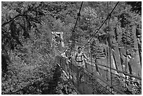 Hikers cross suspension bridge over Lava Canyon. Mount St Helens National Volcanic Monument, Washington (black and white)