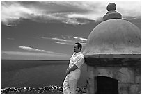 Man leaning against a lookout turret, Fort San Felipe del Morro. San Juan, Puerto Rico (black and white)