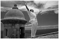 Man standing next to a lookout turret, with arms spread, El Morro Fortress. San Juan, Puerto Rico (black and white)