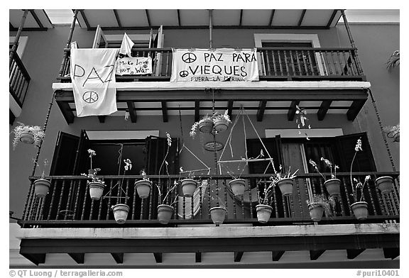 Facade of house painted in blue with pots, balconies and anti-war signs. San Juan, Puerto Rico (black and white)