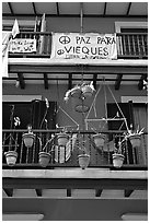 Facade of house painted in blue with plant pots and balconies. San Juan, Puerto Rico (black and white)