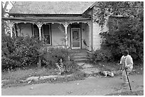 Woman walking dog in front of a crooked house. Selma, Alabama, USA ( black and white)
