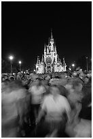 Crowds walking away from Cinderella Castle at night. Orlando, Florida, USA (black and white)