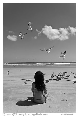 Girl sitting on beach with birds flying, Jetty Park. Cape Canaveral, Florida, USA (black and white)
