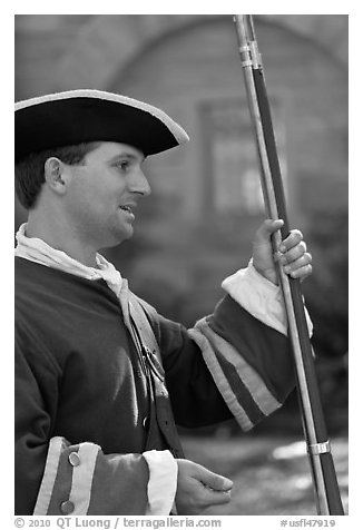 Man dressed as a Spanish soldier in the 18th century demonstrates gun, Fort Matanzas National Monument. St Augustine, Florida, USA (black and white)
