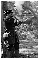 Man in period costume fires smooth bore musket, Fort Matanzas National Monument. St Augustine, Florida, USA ( black and white)