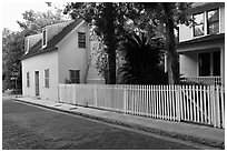 White picket fence and houses on cobblestone street. St Augustine, Florida, USA ( black and white)