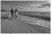Couple jogging on beach,  Miami Beach. Florida, USA ( black and white)